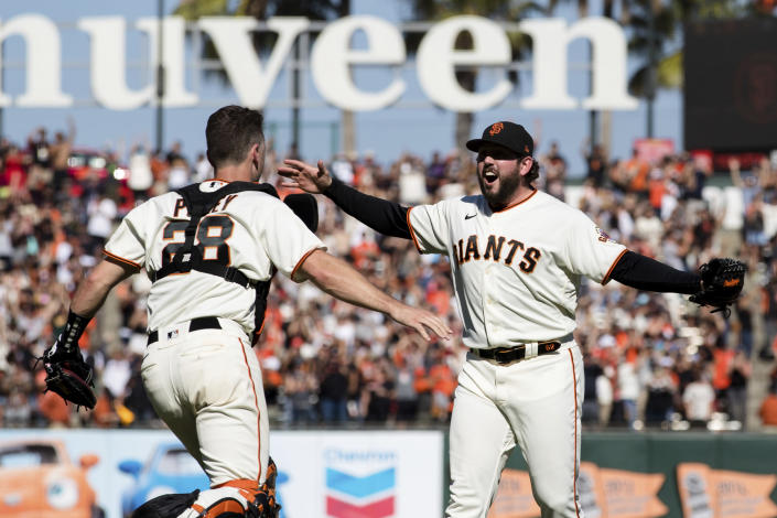 San Francisco Giants closing pitcher Dominic Leone, right, and catcher Buster Posey (28) react after defeating the San Diego Padres in a baseball game in San Francisco, Sunday, Oct. 3, 2021. (AP Photo/John Hefti)