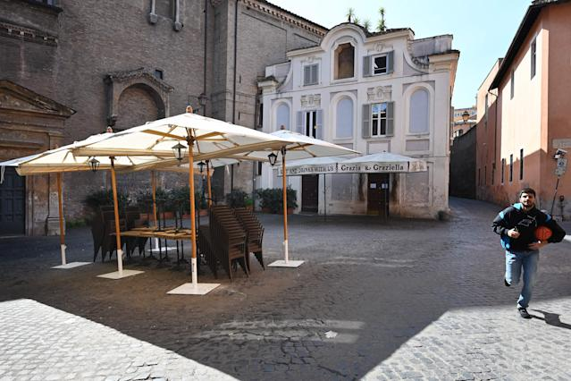 A man runs past an empty restaurant on Piazza di Sant'Egidio in the Trastevere district of Rome on March 10, 2020. (Credit: Alberto Pizzoli/AFP)