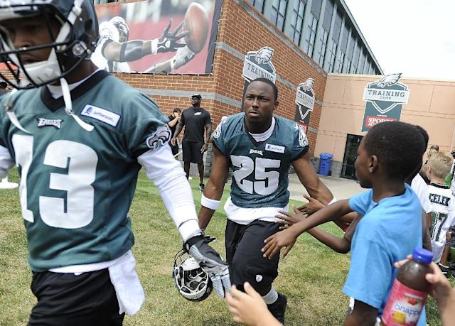 Philadelphia Eagles' LeSean McCoy (25) and Damaris Johnson greet fans as they take the field during NFL football training camp on Saturday, July 26, 2014, in Philadelphia. (AP Photo/Michael Perez)