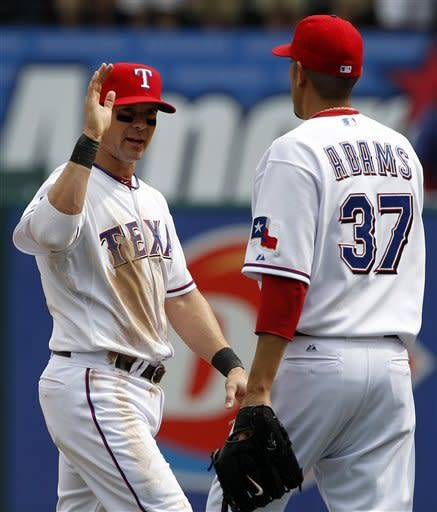 Texas Rangers' Michael Young, left, and Mike Adams (37) congratulate each other following their baseball game against the Seattle Mariners, Thursday, April 12, 2012, in Arlington, Texas. Young hit a two-run home run and had four RBIs to back Derek Holland, leading the Rangers over the Mariners 5-3. (AP Photo/Tony Gutierrez)