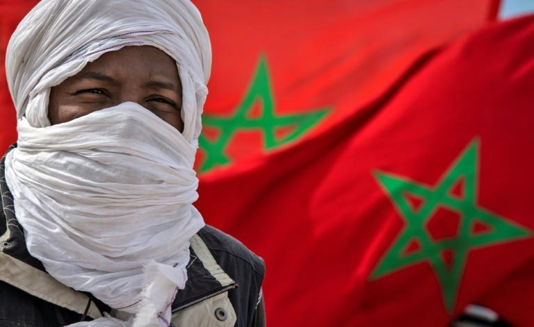 A tribesman stand in front of a Moroccan flags near the border in Guerguerat located in Western Sahara in November 2020