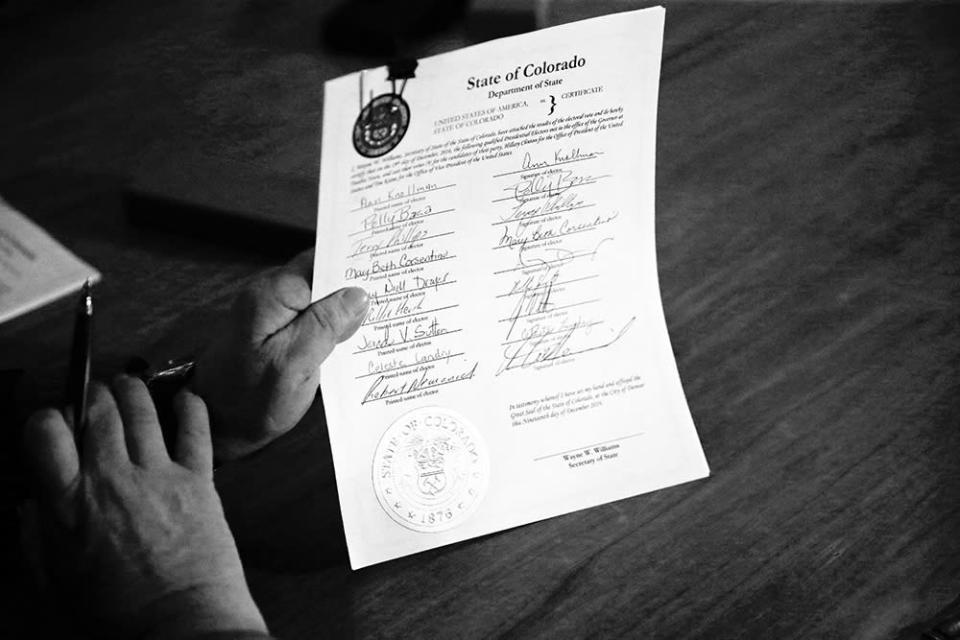 "A Colorado elector holds a signed vote certificate during the electoral vote at the Capitol in Denver on Dec. 19, 2016. The state's nine Democratic electors cast their votes for Hillary Clinton after one elector was removed from the panel for voting for another candidate, which spawned a lawsuit to which the Supreme Court affirmed the constitutionality of removing ""faithless electors."""