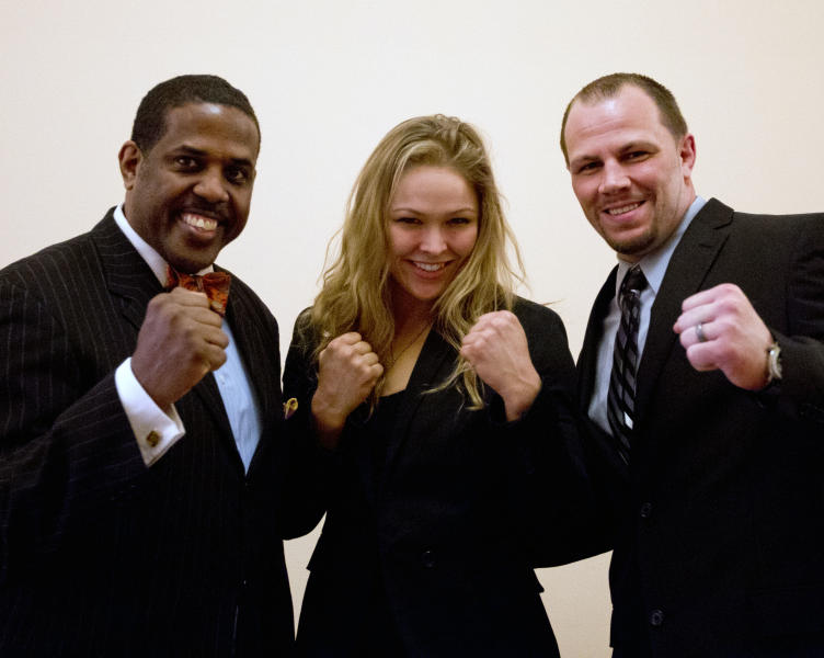 Sen. Kevin Parker, D-Brooklyn, left, poses with mixed martial arts athletes Ronda Rousey, center, and Nick Catone at the Capitol in Albany, N.Y., on Wednesday, April 18, 2012. The state Senate is expected to approve legislation again to make New York the 46th state to legalize and regulate the sport, though opposition remains in the state Assembly. (AP Photo/Mike Groll)