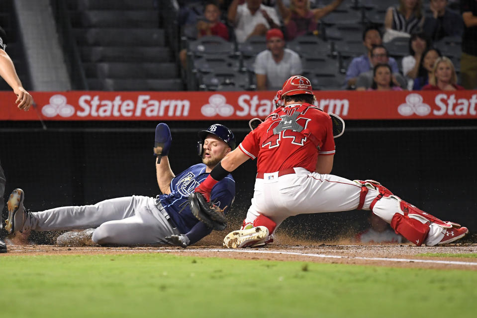 Tampa Bay Rays' Austin Meadows, left, is tagged out by Los Angeles Angels catcher Kevan Smith as he tries to score on a single by Jesus Aguilar during the first inning of a baseball game Friday, Sept. 13, 2019, in Anaheim, Calif. (AP Photo/Mark J. Terrill)