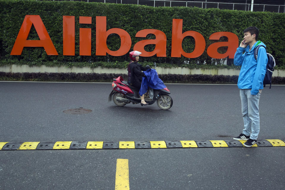 FILE - In this May 27, 2016, file photo, a man talks on his phone as a woman rides on an electric bike past a company logo at the Alibaba Group headquarters in Hangzhou in eastern China's Zhejiang province. China's market regulator on Monday, Dec. 14, 2020 said it fined Alibaba Group and a Tencent Holdings-backed company for failing to seek approval before proceeding with some acquisitions. (AP Photo/Ng Han Guan, File)