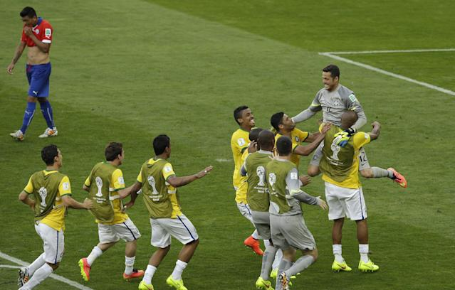 Brazil's goalkeeper Julio Cesar, top right, is congratulated by his teammates as Chile's Gonzalo Jara, top left, walks past after the World Cup round of 16 soccer match between Brazil and Chile at the Mineirao Stadium in Belo Horizonte, Brazil, Saturday, June 28, 2014. Brazil won 3-2 on penalties after the match ended 1-1 draw after extra-time. (AP Photo/Hassan Ammar)