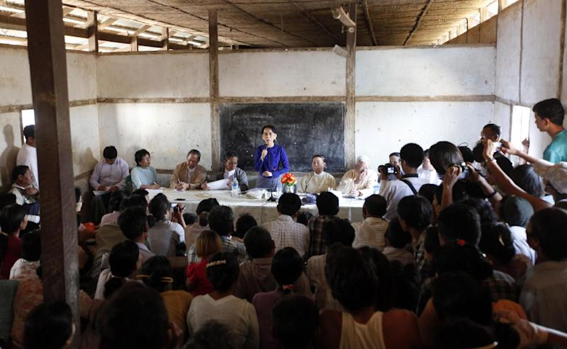 Myanmar opposition leader Aung San Suu Kyi, center, speaks during a meeting with villagers at a school during a visit to an area near the Letpadaung copper mine, in Monywa township, 760 kilometers (450 miles) north of Yangon, central Myanmar, Wednesday, March 13, 2013. Opponents of the nearly $1 billion copper mine in northwestern Myanmar expressed outrage Tuesday over a government-ordered report that said the project should continue and that refrained from demanding punishment for police involved in a violent crackdown on protesters. Suu Kyi chaired the investigation commission that produced the report, which was released Monday night. (AP Photo/Khin Maung Win)