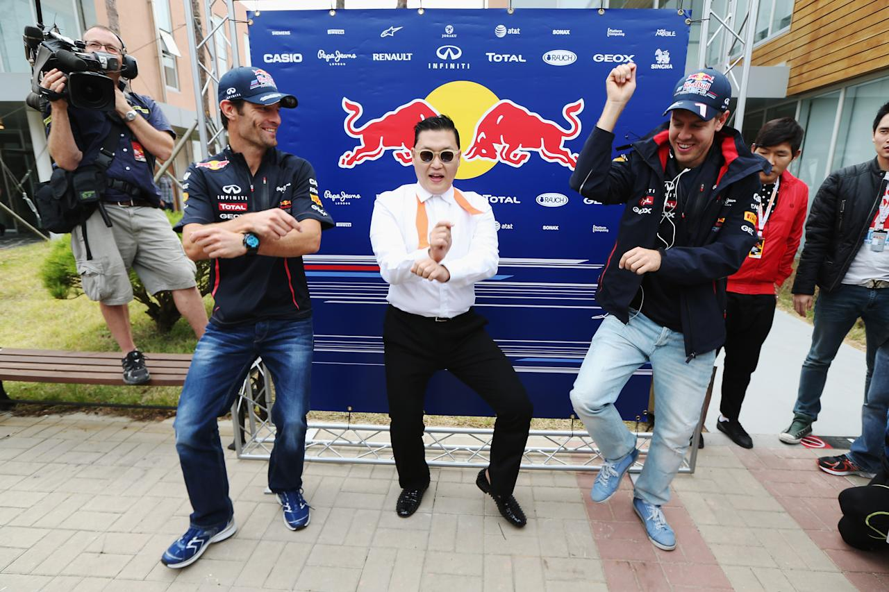 YEONGAM-GUN, SOUTH KOREA - OCTOBER 14:  Korean rapper Psy (C) teaches Red Bull Racing drivers Mark Webber (L) and Sebastian Vettel (R) the Gangnam Style dance in the paddock before the Korean Formula One Grand Prix at the Korea International Circuit on October 14, 2012 in Yeongam-gun, South Korea.  (Photo by Mark Thompson/Getty Images)