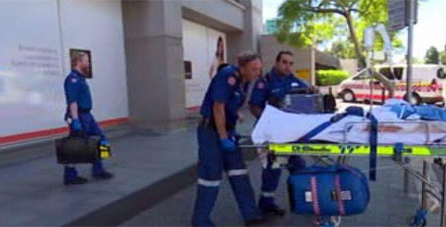 Ambulance staff take the woman away from The Cosmetic Institute in Parramatta. Photo: 7News