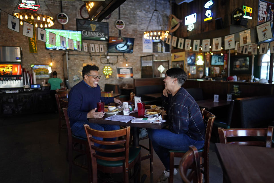 Tasha Arevalo, right, laughs with Joseph Butler while eating at Mo's Irish Pub, Tuesday, March 2, 2021, in Houston. Texas Gov. Greg Abbott announced that he is lifting business capacity limits and the state's mask mandate starting next week. (AP Photo/David J. Phillip)