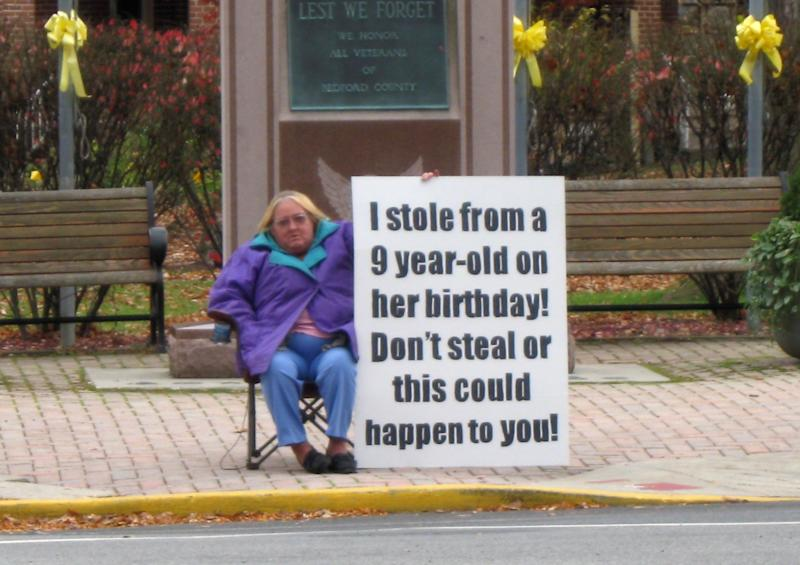FILE-In this Tuesday, Nov. 3, 2009 file photo provided by the Bedford County, Pa. District Attorney's Office shows Evelyn Border holding a sign in front of the Bedford County courthouse in Bedford, Pa.  Bedford County District Attorney Bill Higgins says in exchange for Border and her daughter, Tina Griekspoor, both of Bedford, agreeing to hold the signs, he'll asked for probation instead of jail when they pleaded guilty. Higgins says they swiped a gift card which a girl set on a shelf while a WalMart employee helped her. (AP Photo/Bedford County District Attorney's Office, File) **NO SALES**