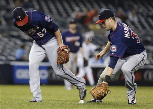 Minnesota Twins relief pitcher Ryan Pressly (57) and first baseman Justin Morneau (33) chase down a sacrifice bunt by New York Yankees' Chris Stewart in the fifth inning of a baseball game Friday, July 12, 2013, in New York. (AP Photo/Frank Franklin II)