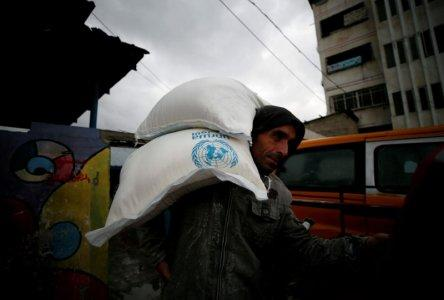 FILE PHOTO: A Palestinian man carries sacks of flour outside a United Nations food distribution center in Al-Shati refugee camp in Gaza City December 6, 2017. REUTERS/Mohammed Salem/File Photo