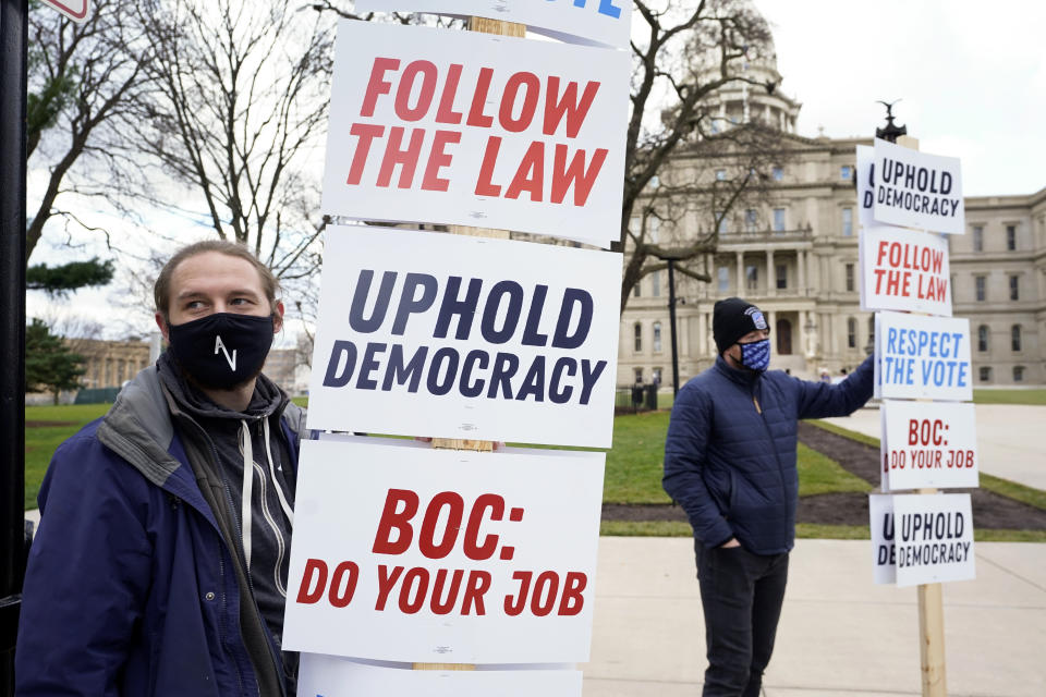 Joscha Weese, left, stands outside the Capitol building during a rally in Lansing, Mich., Saturday, Nov. 14, 2020. Michigan's elections board is scheduled to meet to certify the state's presidential election results Monday. (AP Photo/Paul Sancya)