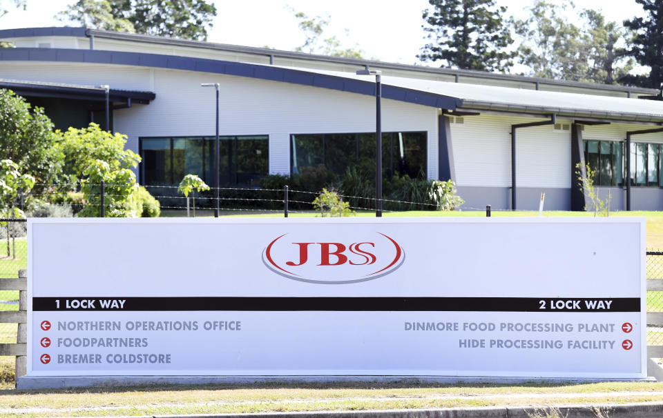 In this May 12, 2020, photo, the company logo sign sits at the entrance to the JBS Australia's Dinmore meatworks facility, west of Brisbane. Thousands of Australian meat workers had no work for a second day on Tuesday, June 1, 2021, after a cyberattack crippled the world's largest meat processing company. A government minister said it might be days before production resumes. (Dan Peled/AAP Image via AP)