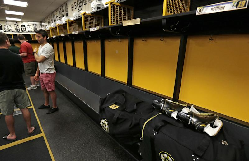 Boston Bruins center Patrice Bergeron gestures towards his right shoulder as he talks with reporters in the team locker room, Tuesday, July 2, 2013, in Boston. Bergeron played through a multiple injuries including a broken rib, separated shoulder and hole in his lung during the Stanley Cup Championship. (AP Photo/Charles Krupa)
