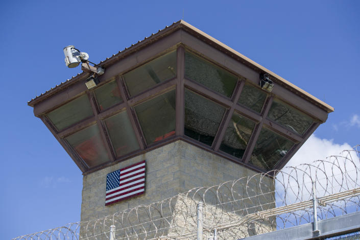 FILE - In this June 17, 2019, file photo reviewed by U.S. military officials, an American flag is displayed on the control tower of the Camp VI detention facility in Guantanamo Bay Naval Base, Cuba. The White House says it intends to shutter the prison on the U.S. base in Cuba, which opened in January 2002 and where most of the 39 men still held have never been charged with a crime. (AP Photo/Alex Brandon, File)