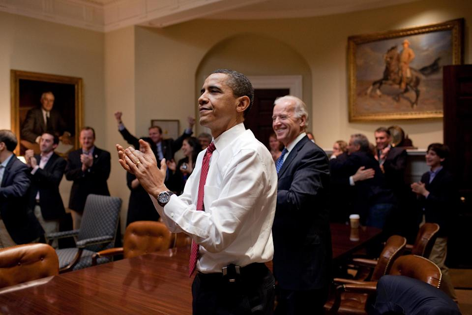 Former President Barack Obama, then Vice President Joe Biden and senior staff applaud in the Roosevelt Room of the White House, as the House passes the health care reform bill, March 21, 2010. - Credit: The White House