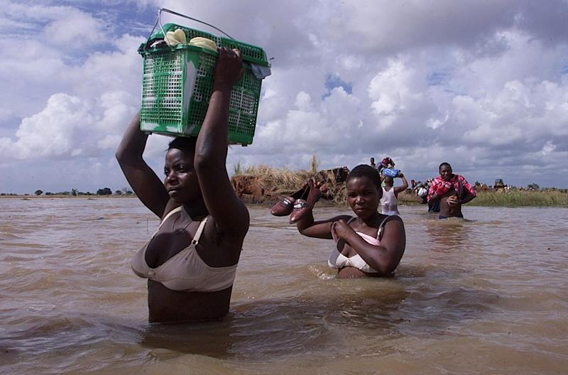 Mozambican women cross a flooded area close to the town of Palmeira, some 150 kilometers north of Maputo, in 2000 (AFP Photo/Yoav Lemmer)