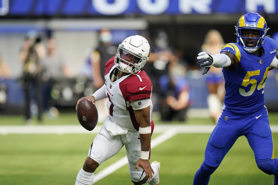 Arizona Cardinals quarterback Kyler Murray, left, avoids the rush from Los Angeles Rams outside linebacker Leonard Floyd during the first half in an NFL football game Sunday, Oct. 3, 2021, in Inglewood, Calif. (AP Photo/Jae C. Hong)