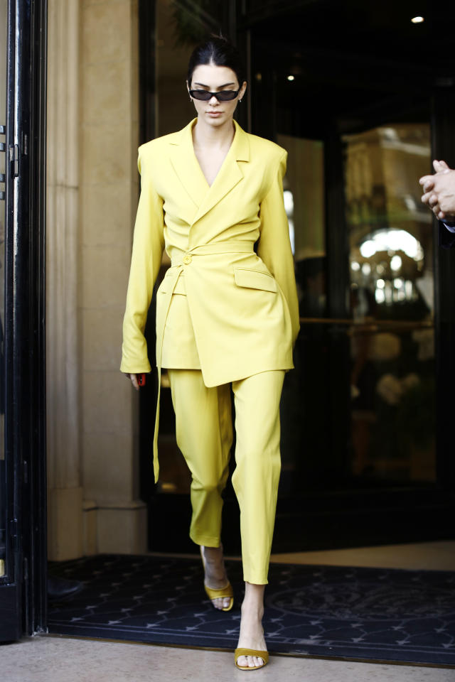 <p>Kendall Jenner certainly wasn't looking to blend in wearing this neon yellow trouser suit by House of Holland. [Photo: Getty] </p>