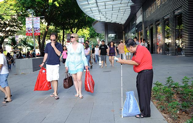 A man sells tissue packets on Orchard Road in Singapore. (Yahoo photo)