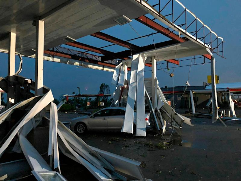 A car is trapped under the fallen metal roof of the Break Time gas station and convenience store in tornado-hit Jefferson City, Mo., May 23, 2019. (Photo: AP Photo/David A. Lieb)