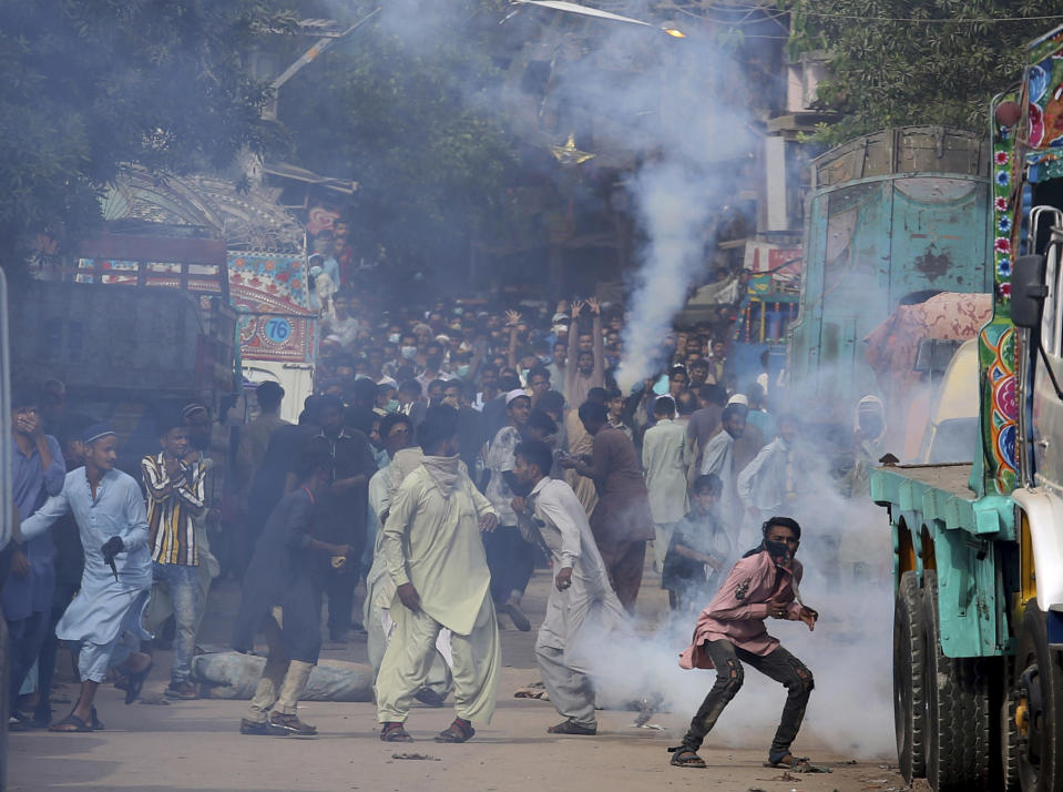 Supporters of Tehreek-e-Labiak Pakistan, a banned Islamist party, react after police fire tear gas to disperse them while protesting the arrest of their party leader Saad Rizvi, in Karachi, Pakistan, Monday, April 19, 2021. The outlawed Islamist political group freed 11 policemen almost a day after taking them hostage in the eastern city of Lahore amid violent clashes with security forces, the country's interior minister said Monday. (AP Photo/Fareed Khan)