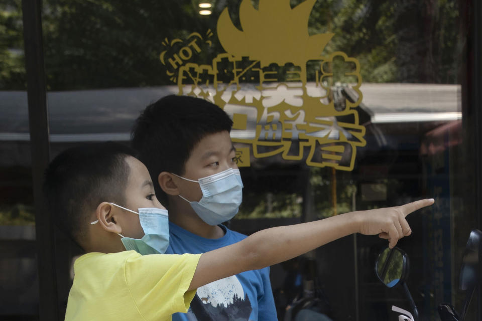 Children wearing masks to curb the spread of the new coronavirus chat outside a restaurant in Beijing on Friday, June 19, 2020. China declared a fresh outbreak in Beijing under control after numbers for new cases stabilized as hundreds of thousands are tested. (AP Photo/Ng Han Guan)