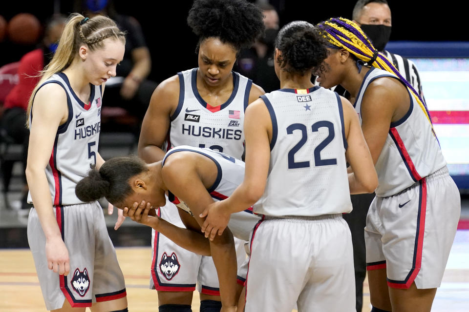 Connecticut's Aubrey Griffin is surrounded by her teammates as she holds her face after being injured during the first half of an NCAA college basketball game against the DePaul Sunday, Jan. 31, 2021, in Chicago. (AP Photo/Charles Rex Arbogast)
