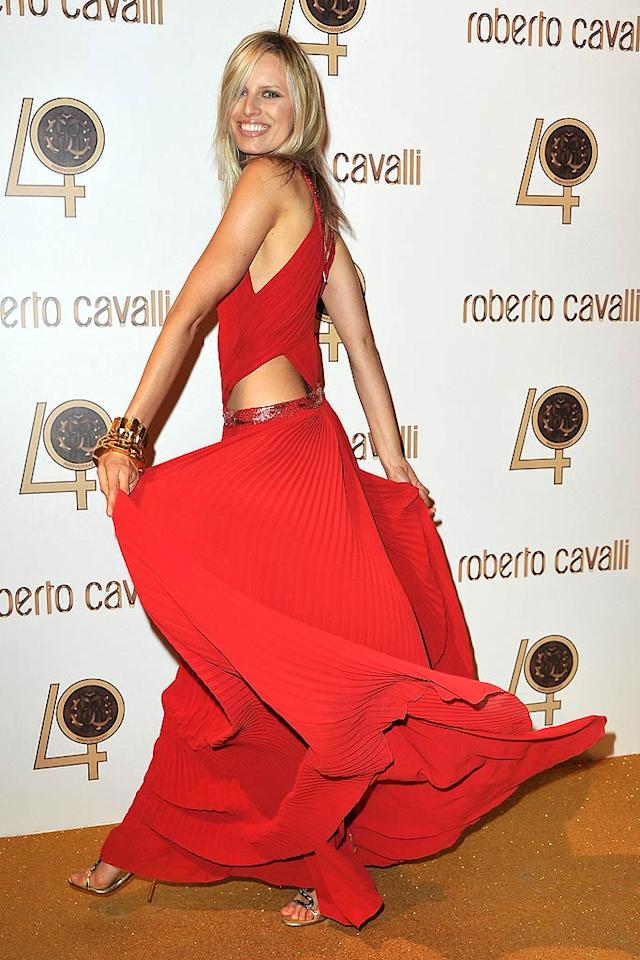 "Model Karolina Kurkova flaunted a playful look consisting of a radiant red dress with cutouts and accordion pleats, minimal gold accoutrements, and wild, free-flowing locks. Pascal Le Segretain/<a href=""http://www.gettyimages.com/"" target=""new"">GettyImages.com</a> - September 29, 2010"