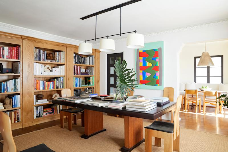The home's library doubles as an occasional dining room (Mr. Bennett typically hosts dinners outdoors, in a garden with sweeping city views). An Art Deco table by Viennese designer Paul T. Frankl, placed below a Thomas O'Brien Billiard light fixture, was paired with wood-and-leather chairs by Carlo Scarpa, designed in the '70s for Bernini. The back wall features a painting by Sadie Benning, part of a growing collection of contemporary American art.