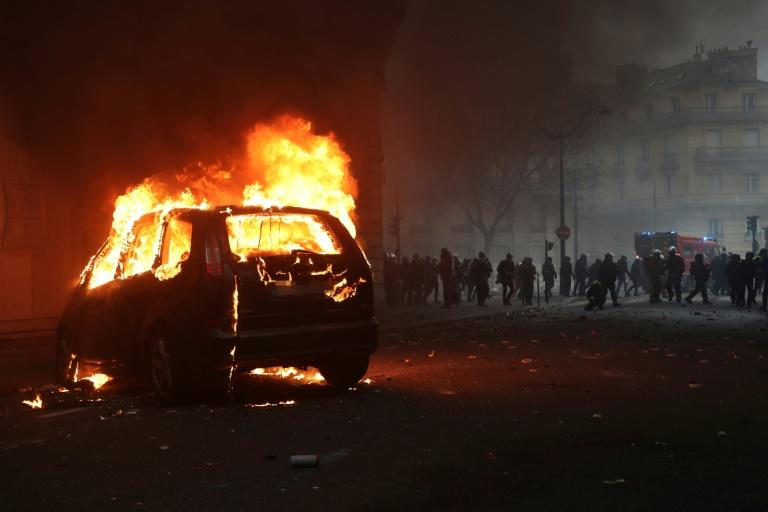 A car burning overnight during demonstrations in Paris which saw police and protesters clash