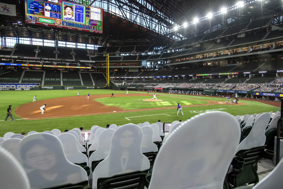 """The Texas Rangers and the Colorado Rockies play in front of cardboard cutouts depicting fans, dubbed """"DoppleRangers,"""" during the first inning of an opening day baseball game Friday, July 24, 2020, in Arlington, Texas. (AP Photo/Jeffrey McWhorter)"""