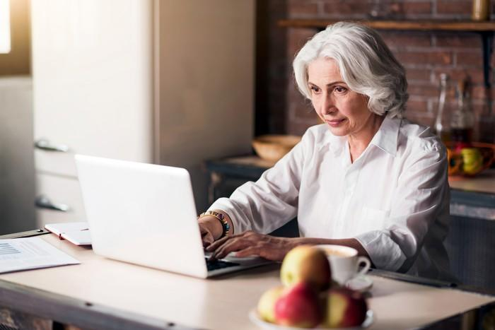 A woman types on her laptop in the kitchen