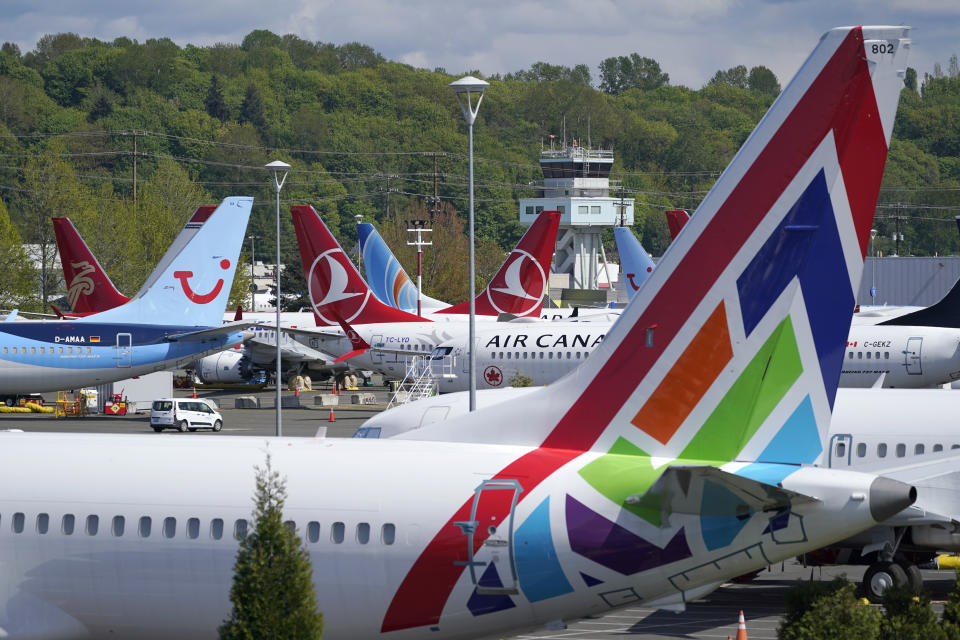 FILE — In this April 26, 2021, file photo Boeing 737 Max airplanes sit parked in a storage lot, near Boeing Field in Seattle. The Boeing Co. told employees, Tuesday, Oct. 12, 2021, that they must be vaccinated against COVID-19 or possibly be fired. The Seattle Times reports the deadline for workers at the aerospace giant is Dec. 8. (AP Photo/Ted S. Warren, File)