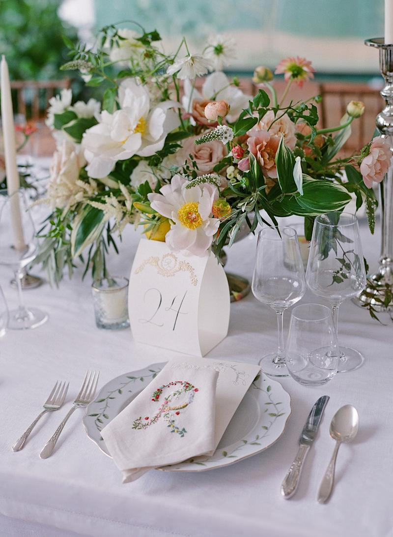Inspired by the romanticism of the lush gardens, we loved the idea of embroidering the linens with a floral R, and our menus were embossed with lily of the valley.