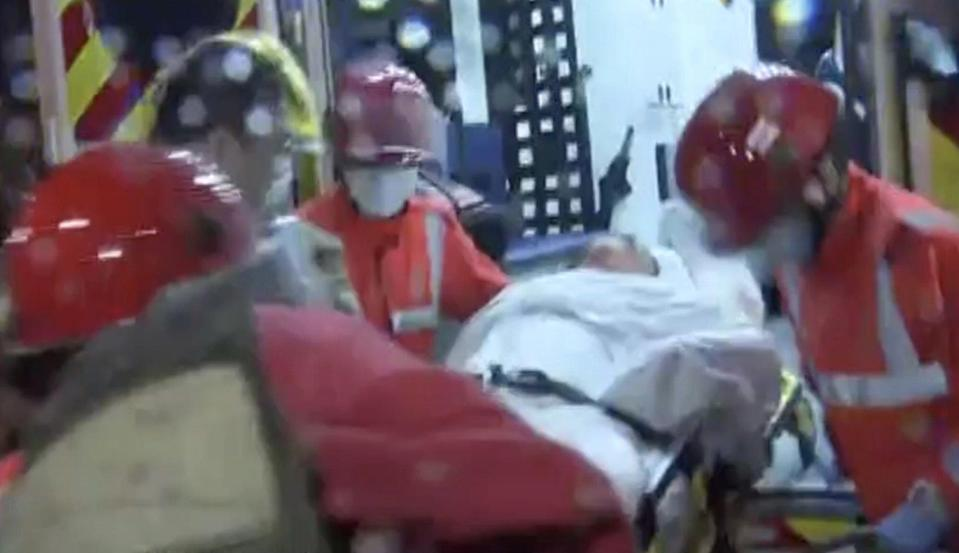 Firefighters take a victim to a waiting ambulance on Friday morning in Hong Kong's Kwun Tong district. Photo: Now TV