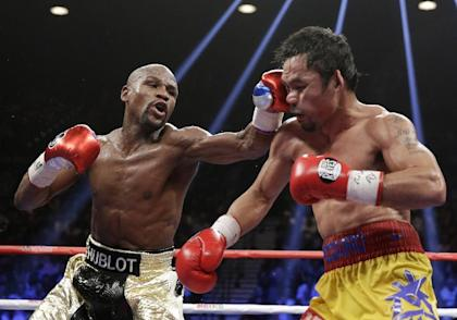 Floyd Mayweather, left, hits Manny Pacquiao, during their welterweight title fight. (AP)