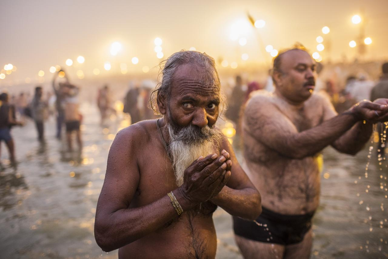 ALLAHABAD, INDIA - JANUARY 14: Hindu devotees bathe in the waters of the holy Ganges river during the auspicious bathing day of Makar Sankranti of the Maha Kumbh Mela on January 14, 2013 in Allahabad, India. The Maha Kumbh Mela, believed to be the largest religious gathering on earth is held every 12 years on the banks of Sangam, the confluence of the holy rivers Ganga, Yamuna and the mythical Saraswati. The Kumbh Mela alternates between the cities of Nasik, Allahabad, Ujjain and Haridwar every three years. The Maha Kumbh Mela celebrated at the holy site of Sangam in Allahabad, is the largest and holiest, celebrated over 55 days, it is expected to attract over 100 million people. (Photo by Daniel Berehulak/Getty Images)