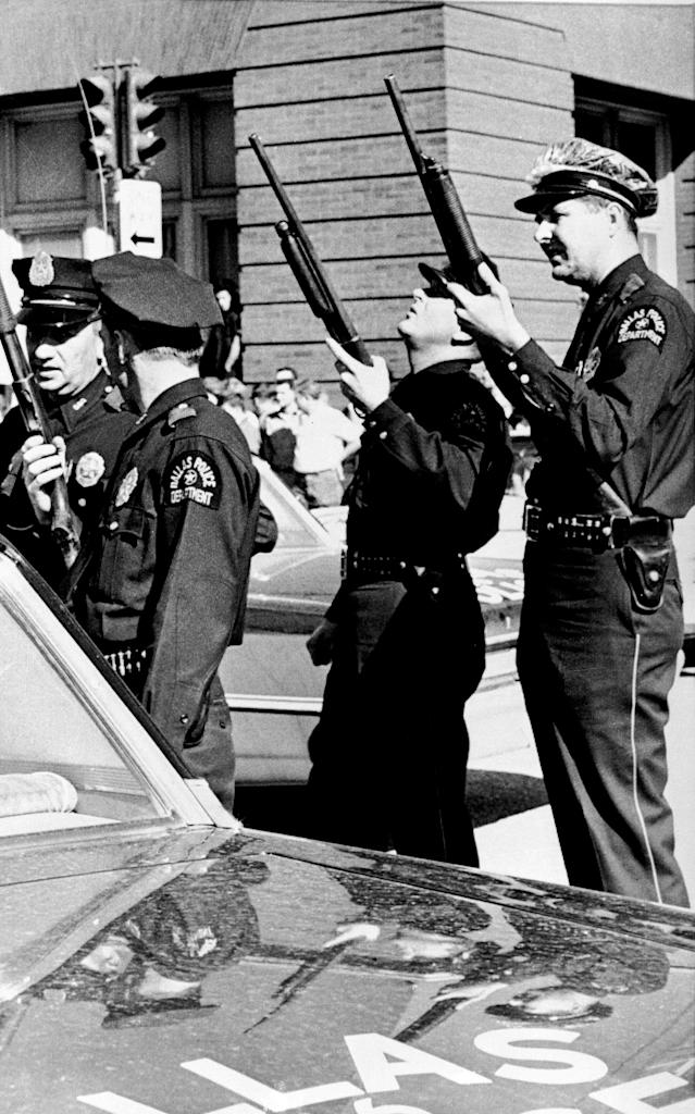 <p>Police officers with guns ready look up the building where the shot came from that killed U.S. President John F. Kennedy while he was riding in an open limousine through downtown Dallas, Texas, on Nov. 22, 1963. (Photo: AP) </p>