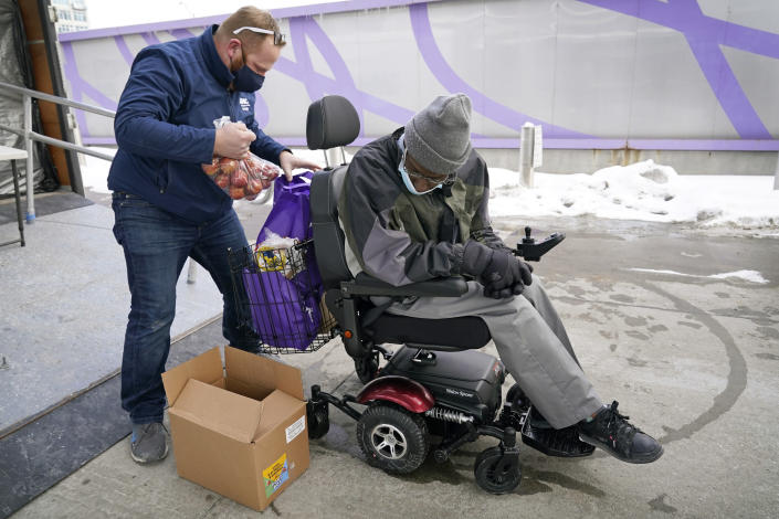 Des Moines Area Religious Council operations manager Joe Dolack, left, loads a Farmers to Families Food Box for Thomas Washington, of Des Moines, Iowa, at a mobile food pantry stop, Thursday, Feb. 18, 2021, in Des Moines, Iowa. Agricultural groups and anti-hunger organizations are pushing the Biden administration to continue the Farmers to Families Food Box program launched by President Donald Trump that spent $6 billion to prevent farmers from plowing under food and instead provide it to millions of Americans left reeling by the coronavirus pandemic. (AP Photo/Charlie Neibergall)