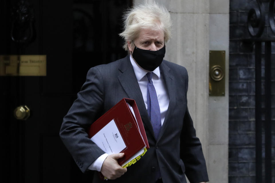 Britain's Prime Minister Boris Johnson leaves Downing Street to attend the weekly session of PMQs in parliament in London, Wednesday, Jan. 20, 2021. (AP Photo/Kirsty Wigglesworth)