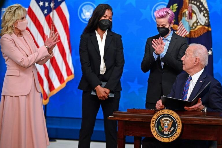 US President Joe Biden, with (L-R) his wife Jill Biden and US soccer stars Margaret Purce and Megan Rapinoe looking on, signed a proclamation on Equal Pay Day 2021