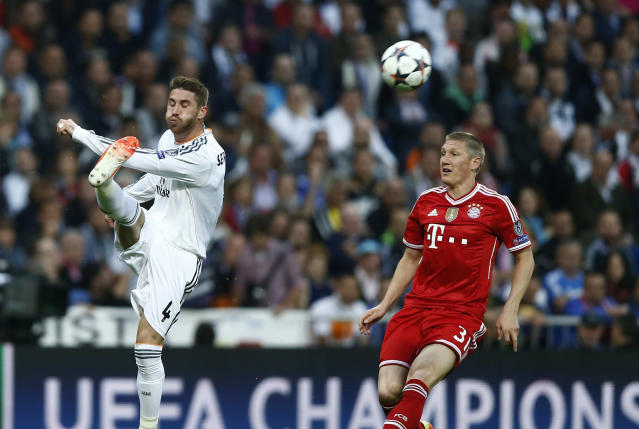 Real's Sergio Ramos kicks the ball next to Bayern's Bastian Schweinsteiger, right, during a first leg semifinal Champions League soccer match between Real Madrid and Bayern Munich at the Santiago Bernabeu stadium in Madrid, Spain, Wednesday, April 23, 2014. (AP Photo/Andres Kudacki)