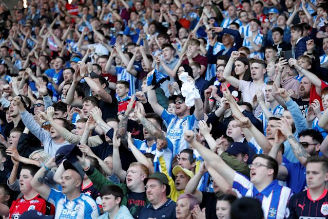 "Soccer Football - Premier League - Huddersfield Town vs Arsenal - John Smith's Stadium, Huddersfield, Britain - May 13, 2018 Huddersfield Town fans celebrate at the end of the match Action Images via Reuters/Andrew Boyers EDITORIAL USE ONLY. No use with unauthorized audio, video, data, fixture lists, club/league logos or ""live"" services. Online in-match use limited to 75 images, no video emulation. No use in betting, games or single club/league/player publications. Please contact your account representative for further details."