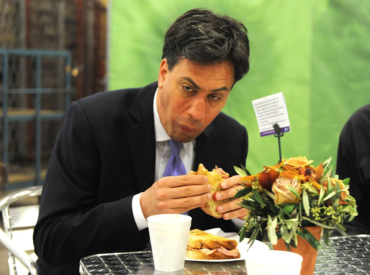 <p>Ed Miliband tucks into a bacon sandwich on a morning trip to buy flowers for his wife. </p>