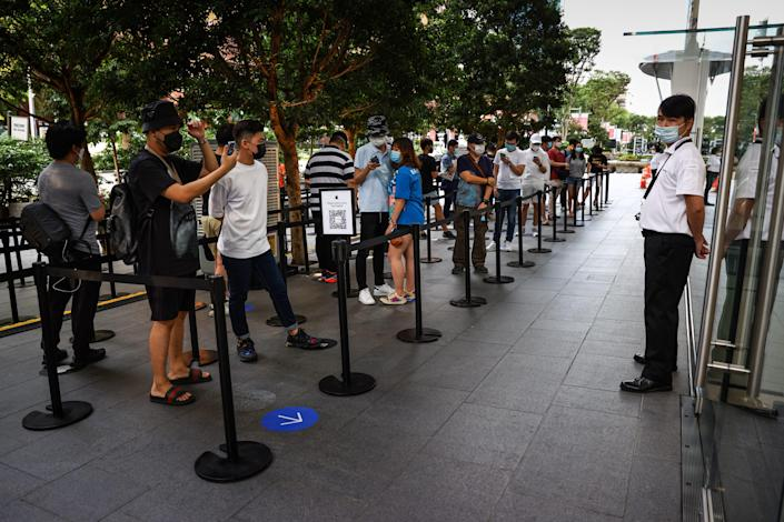 People wait in line to purchase newly released products at the Apple Store in Orchard Road on September 24, 2021 in Singapore.