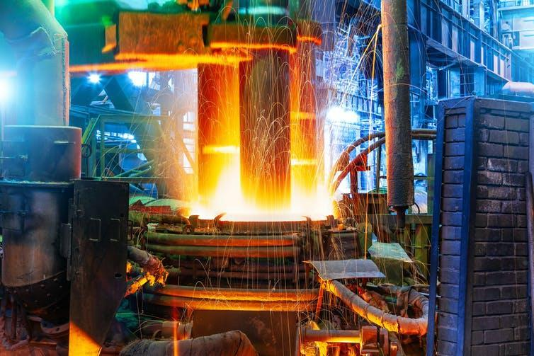 Inside the steelworks, sparks fly from the white heat of a furnace.
