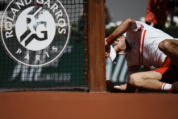 Serbia's Novak Djokovic lays on the clay after falling as he plays Stefanos Tsitsipas of Greece during their final match of the French Open tennis tournament at the Roland Garros stadium Sunday, June 13, 2021 in Paris. (AP Photo/Thibault Camus)
